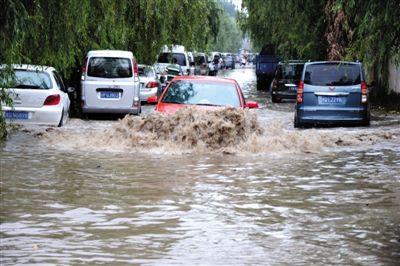 """昨日凌晨的一场降雨,让朝阳区王四营乡王四营村的一条道路严重积水,行人和车辆""""趟河""""而过。拍者 王青"""