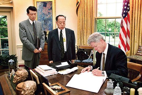 1999 年 5 月 13 日,克林顿在白宫会见李肇星(中)等。在李肇星的要求下,他在吊唁簿上写下道歉的话,并签下自己的名字。