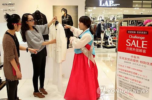 资料图片:喜迎中秋节,乐天百货店首尔总店的工作人员身着韩服(韩国传统服装)向中国游客推介产品。摄于2013年9月29日。(韩联社)
