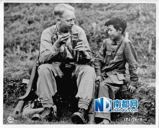 1944年5月6日,来自北达科他州的通信兵摄影师上等兵亚瑟·海吉(Pvt.A rthurW.H edgo)用筷子吃干粮,身旁的小孩李田右(音:Lee Ting Yow )在教他使用筷子。图片由越众历史影像馆提供