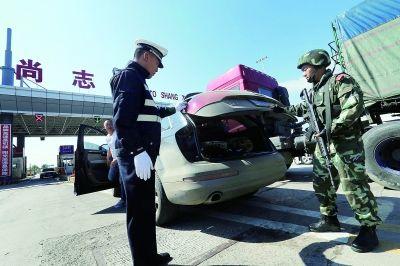 今天上午,黑龙江警方整合巡警、交警、武警等在尚志收费站对驶离车辆进行逐一检查 摄/法制晚报记者 杨益