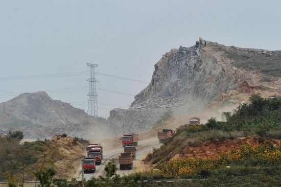 图为众多运输土石方重型卡车穿梭在辽宁省大连新机场建设工地。