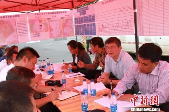 图为张笑春在景谷县永平镇召开现场办公会,指导灾区卫生防疫工作。 张嵩玮 摄