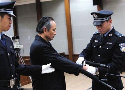 被告人张曙光戴上手铐。昨日,北京市二中院对原铁道部运输局局长、副总工程师张曙光受贿案进行一审宣判,判处其死缓。法院供图