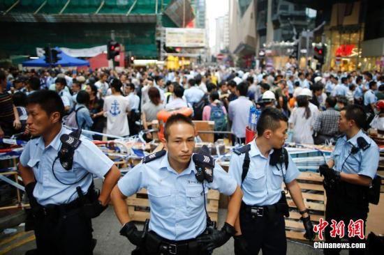 """10月23日下午,香港""""占领中环""""非法集会者在旺角阻挡市民清除路障,引起混乱,警察在现场维持秩序。""""占领中环""""非法集会已进入第26日,香港市民已愤怒不已。中新社发 盛佳鹏 摄"""