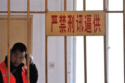 """2014年3月18日,四川省成都市,一犯罪嫌疑人在""""严禁刑讯逼供""""的标牌下接受审讯。图/CFP"""