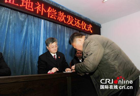 12月19日,匡家村征地补偿款发还仪式在黄夹镇检察室举行,村民签字后领回了被村干部贪污的部分地钱。 摄影:闫昭