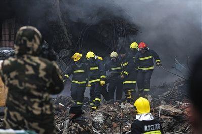 昨日13时左右,殉职消防员遗体被找到,消防员们将战友遗体抬离废墟。1月2日,哈尔滨一仓库大火,5名消防员牺牲。本版摄影/新京报记者 周岗峰