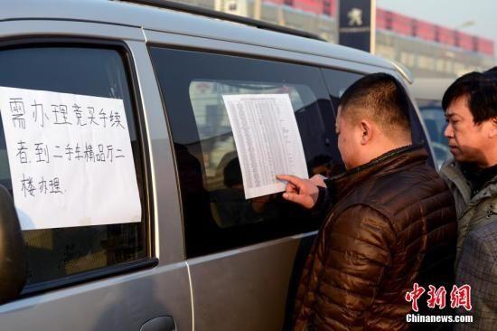 1月23日,北京亚运村汽车交易市场中拓拍卖停车场上人头攒动,市民查看拍卖车辆信息。当日,首场中央层面公车拍卖预展在这里开始举行,标志着中国公车改革迈出实质性一步。三家拍卖公司分别将于1月25日、26日及2月1日举行专场拍卖会。中新社发 郭莎莎 摄