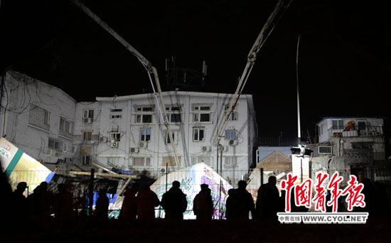 1月24日晚,北京德胜门内大街93号门前塌陷事故现场,抢险人员正在浇筑混凝土。本报记者 陈剑/摄