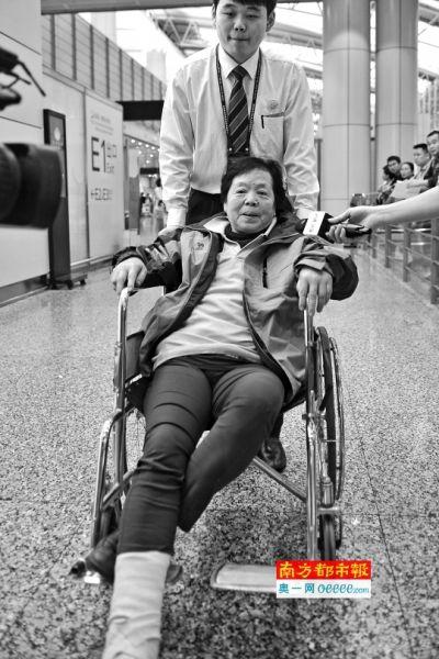 昨晨6时49分,机场工作人员用轮椅推着由加德满都返回广州的牟女士,她右脚在地震中被酒店掉下的天花板砸成骨折。南都记者 梁炜培 摄