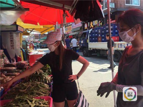 在路口的拐角处,记者见到有几名戴着口罩的中国人正在一蔬菜瓜果摊前挑拣豆角、洋葱等。