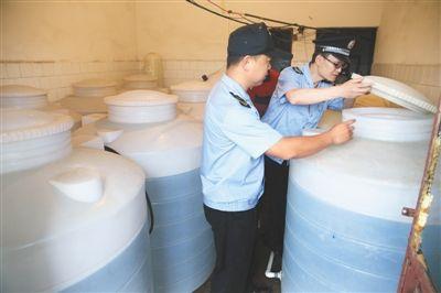 6月初,丰台卢沟桥北路附近,执法人员查处一家假桶装水窝点,数个白色大桶内盛着待灌的水。