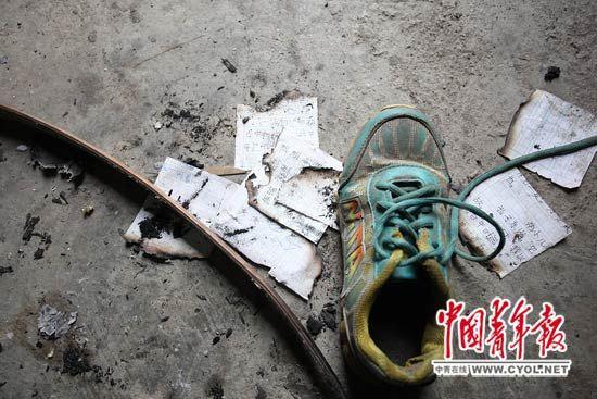 事发现场,一只运动鞋下压着没有燃尽的作业纸。本报记者?白皓/摄