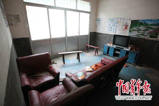 4兄妹住所的客厅里摆放着一台电视机和三个破旧的仿皮沙发。本报记者 白皓摄