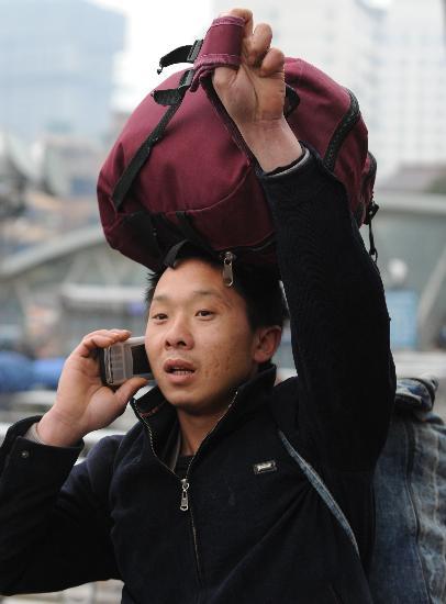 图文:滞留贵阳火车站的旅客用手机与亲友通话