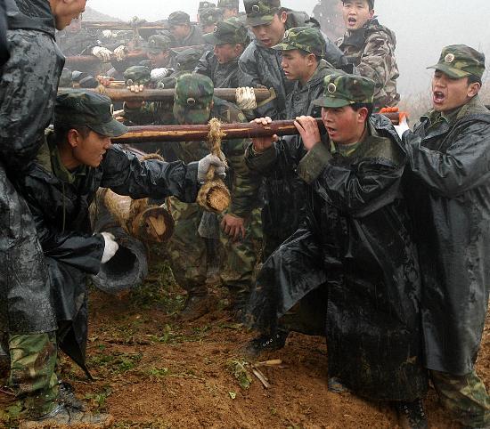 图文:解放军官兵冒着雨雪将电线杆抬上山