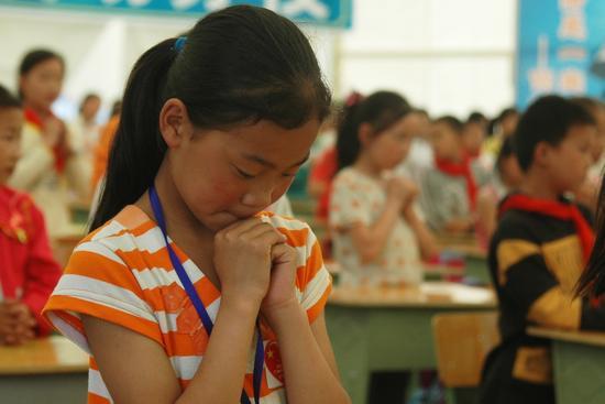 图文:孩子们在为受难的人们祈祷
