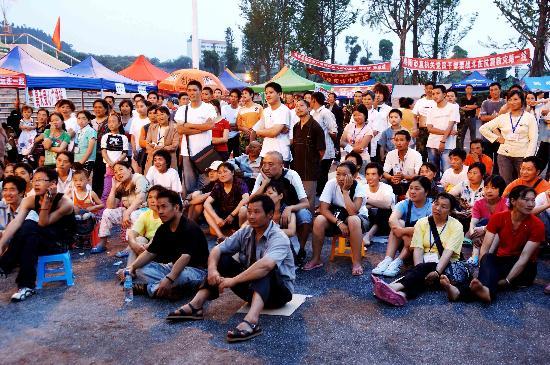图文:安置在九洲体育馆的灾民围在一起看电影