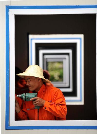 图文:工人在文县一中高考活动板房内安装窗户