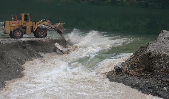 图文:大型工程车将预备的巨石推入渠口