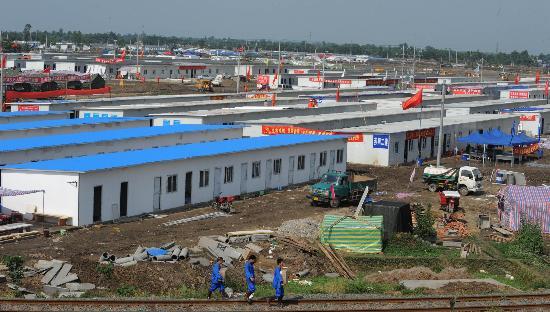 图文:几名工人从新建成的移动板房城前走过
