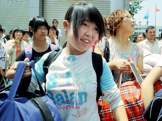 图文:青川中学的一名学生提着行李准备上车