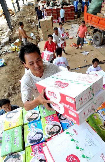图文:配送部门的工作人员在搬运救灾物资