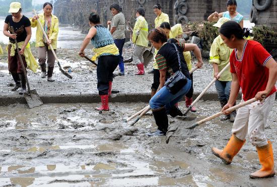 图文:绵阳市民和环卫工人清理洪水留下的泥沙