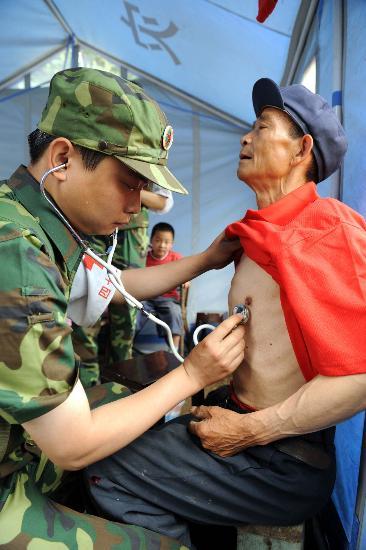 图文:成都军区医生在为一位老人听诊