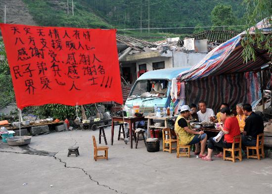 图文:村民在地震棚前悬挂着感谢横幅
