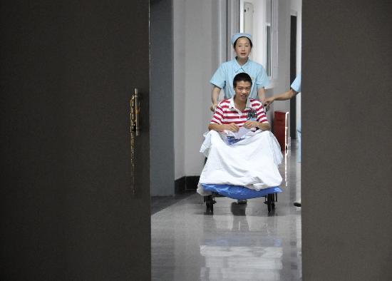 图文:截肢的考生在护士的陪伴下进入考场