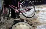图文:大雨过后女士穿高跟鞋提自行车过圆钢管