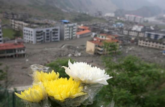 图文:人们在北川老县城遗址摆放菊祭奠亲人
