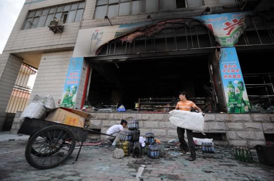 图文:超市经营者在被焚商店外整理货物