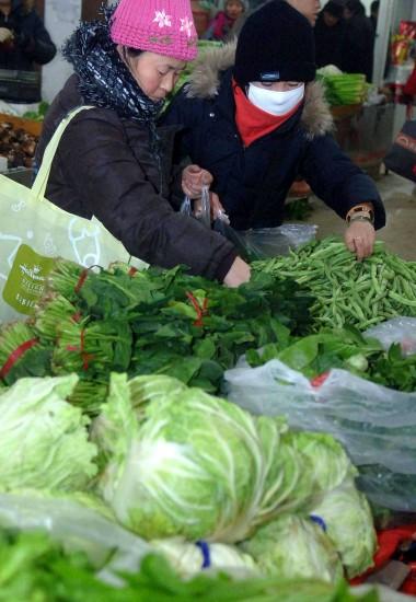 图文:北京市民在一家社区菜市场内选购蔬菜