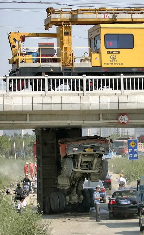 图文:司机忘收车斗致车辆卡在桥下14小时
