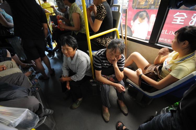 图文:大妈在车上席地而坐年轻女子视若无睹
