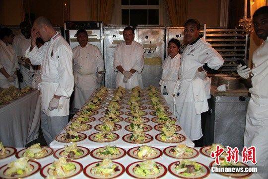"""图为宴会厅一侧的""""后厨"""",人们正准备为宴会上菜。中新社记者 张朔 摄"""