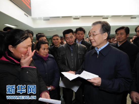 1月24日,中共中央政治局常委、国务院总理温家宝前往国家信访局,与来访群众进行面对面交流,了解他们的困难和要求,并就政府工作听取意见。这是在信访局接待大厅,温家宝总理向来访群众了解他们的诉求情况。新华社记者李涛摄