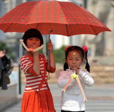 2月27日,两名小朋友在遮阳伞撑起的阴凉下玩耍。
