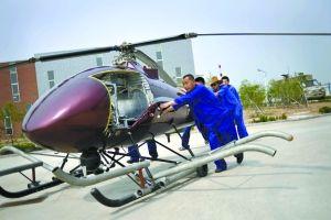 工作人员将被改装好的V750无人直升机推出车间,进行试飞。