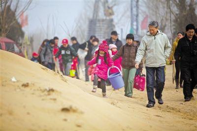 3月17日,河北天漠,家长们带着孩子在去植树的路上。