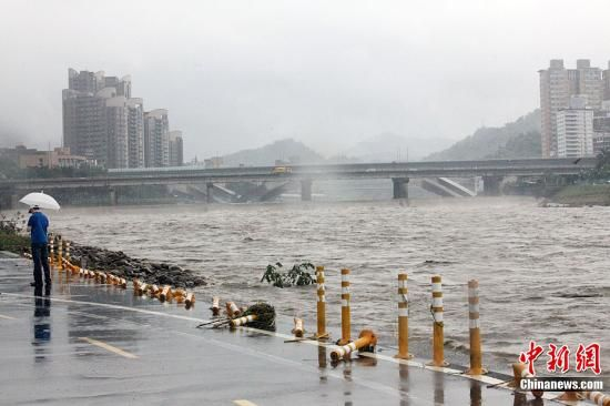 """8月2日,台风""""苏拉""""携带强风豪雨袭击中国台湾,造成多处桥断路毁,低洼地区淹水,及人员伤亡。图为位于中国台湾北部新北市新店区的淡水河中上游新店溪,河水暴涨,水势汹涌。中新社发 黄少华 摄"""