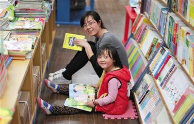 """昨晚10时,来京探亲的山东的李女士带着5岁的女儿琪琪在三联书店读书。4月18日晚开始,三联韬奋书店正式开启""""不打烊书店""""。新京报记者 陈杰 摄"""
