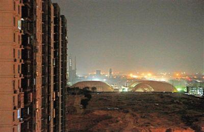 透过双合家园居民家的窗户,可以看到北京焦化厂原址厂区内覆盖着受污染土壤的白色大棚。新京报记者 高玮 摄