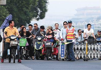 昨日,长安街西单路口,交通协管员指挥人们在伸缩门后等待绿灯,一名黄衣男子骑电动车抢行。新京报记者 尹亚飞 摄