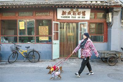26日,前门大栅栏粮食店街,一名街坊经过国营新成削面馆,这个有着60年历史的国营老饭馆因房租问题将在三月底关门。 新京报记者 周岗峰 摄