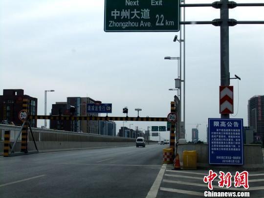 横亘在郑州南三环高架桥上的限高栏,限高2.5米,普通中巴车不能通过。不过此栏一天前又被撤掉,但公告仍在。。 吴扬 摄