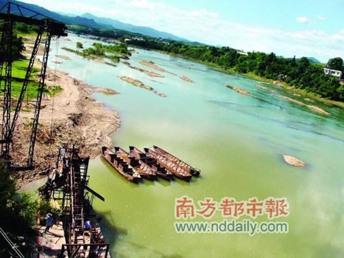 """8月8日,汀江水仍然呈现淡淡的蓝绿色。上杭县环保局一位现场工作人员告诉记者""""铜离子达标了,但多多少少还有点""""。    南都记者 杨传敏 摄"""